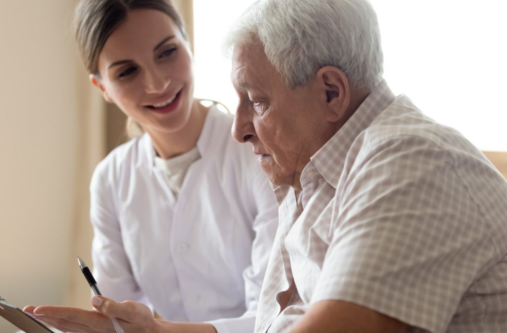An older man being instructed on potential medicare coverage.